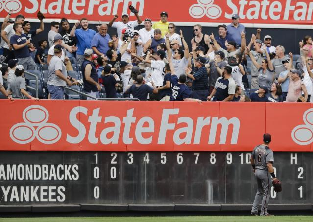 Arizona Diamondbacks left fielder David Peralta watches as fans fight for a ball hit by New York Yankees' Mike Tauchman for a two-run home run during the second inning of a baseball game Wednesday, July 31, 2019, in New York. (AP Photo/Frank Franklin II)