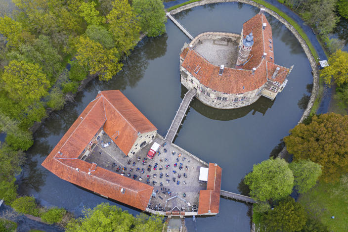 In this aerial view taken with a drone, around 100 spectators are seated during a concert as part of the Coesfeld model region at Burg Vischering, in L'dinghausen, Germany, Saturday, May 8, 2021. The circle presents the guitar virtuosos M. and T. Hoene. Admission was from 17:30 only with a negative coronavirus test. (Guido Kirchner/dpa via AP)