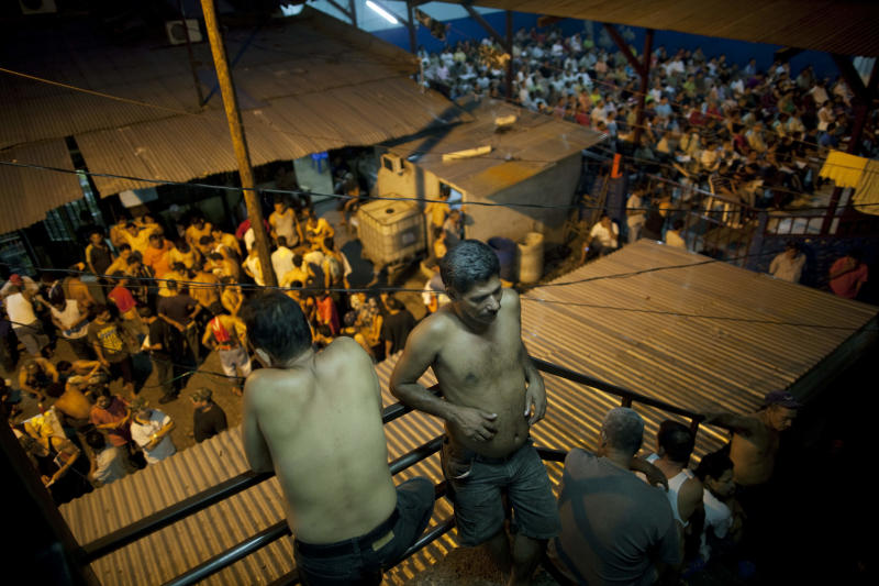 In this May 3, 2012 photo, inmates gather outside their cells in San Pedro Sula Central Corrections Facility in San Pedro Sula, Honduras. Inside one of Honduras' most dangerous and overcrowded prisons, inmates operate a free-market bazaar, selling everything from iPhones to prostitutes. Guards do not cross into the inner sanctum controlled by prisoners, and prisoners do not breach the perimeter controlled by guards. (AP Photo/Rodrigo Abd)