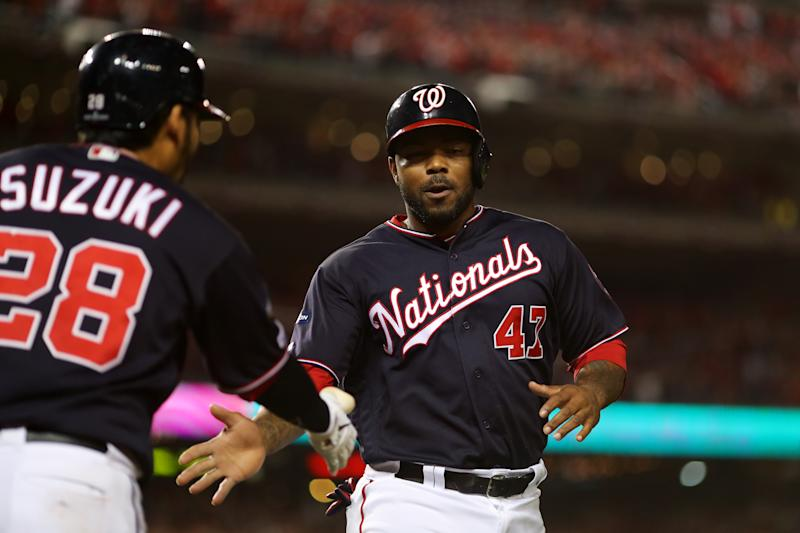 WASHINGTON, DC - OCTOBER 14: Howie Kendrick #47 of the Washington Nationals is greeted by teammate Kurt Suzuki #28 after scoring on a single hit by Ryan Zimmerman #11 during the seventh inning of Game 3 of the NLCS between the St. Louis Cardinals and the Washington Nationals at Nationals Park on Monday, October 14, 2019 in Washington, District of Columbia. (Photo by Alex Trautwig/MLB Photos via Getty Images)