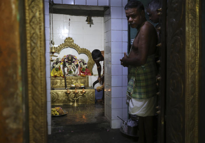 A Hindu priest prepares to break a coconut to offer to a deity during special prayers for U.S. Vice President-elect Kamala Harris ahead of her inauguration, at a temple in Thulasendrapuram, the hometown of Harris' maternal grandfather, south of Chennai, Tamil Nadu state, India, Wednesday, Jan. 20, 2021. A tiny, lush-green Indian village surrounded by rice paddy fields was beaming with joy Wednesday hours before its descendant, Kamala Harris, takes her oath of office and becomes the U.S. vice president. (AP Photo/Aijaz Rahi)