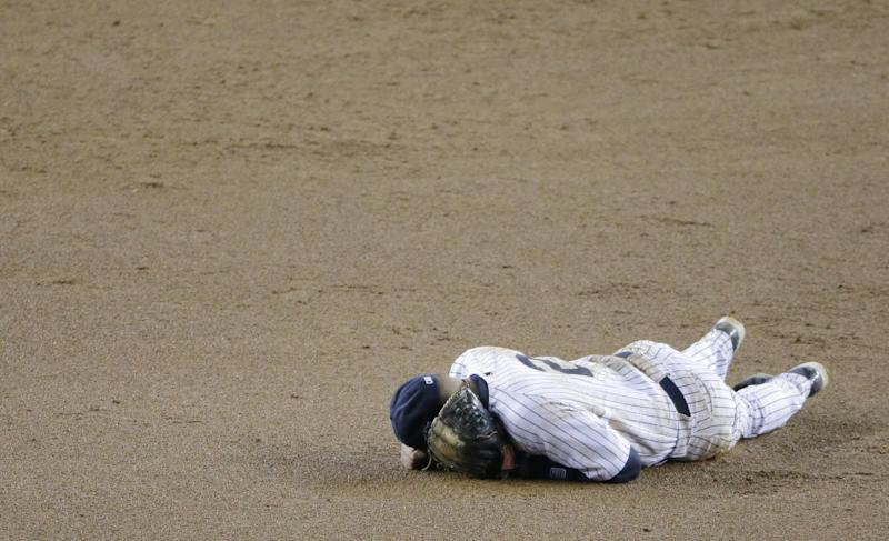New York Yankees shortstop Derek Jeter lays on the infield after injuring himself in the 12th inning of Game 1 of the American League championship series against the Detroit Tigers Sunday, Oct. 14, 2012, in New York. (AP Photo/Charlie Riedel)