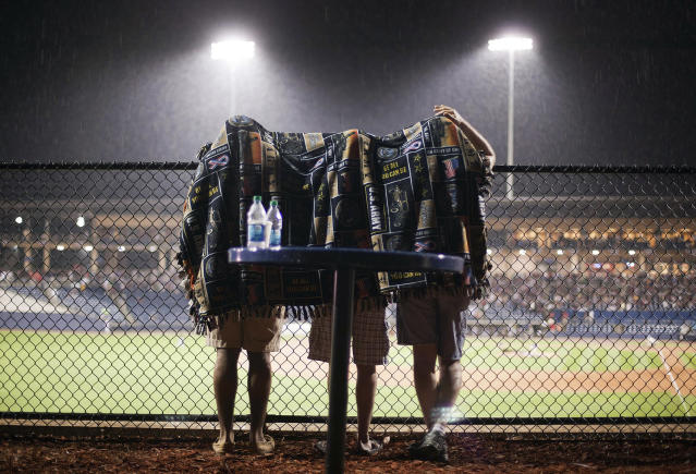<p>Fans take shelter under a blanket during a rain delay in the seventh inning of an exhibition baseball game between the Atlanta Braves and the Atlanta Braves Future Stars on April 3, 2012, in Lawrenceville, Ga. (AP Photo/David Goldman) </p>