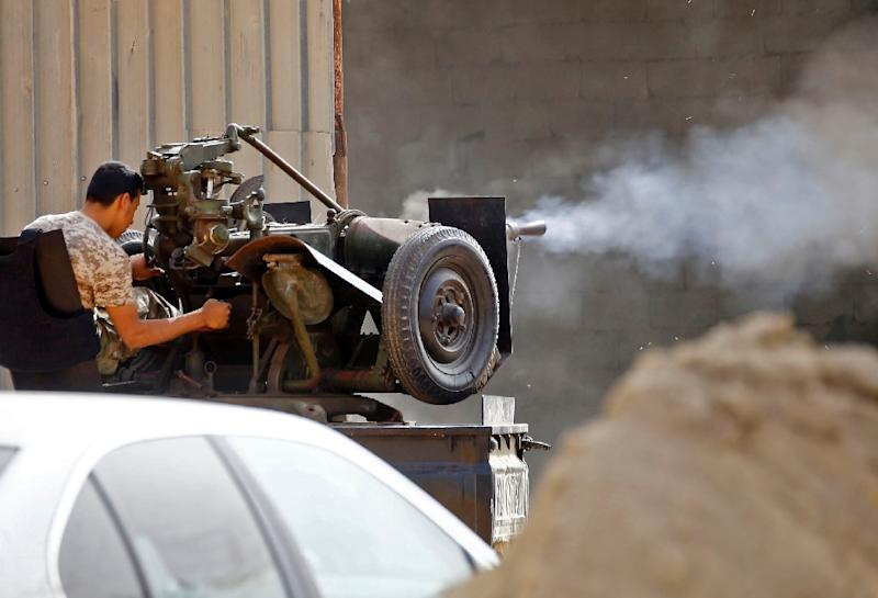 A fighter fires a heavy weapon mounted on a truck towards fighters loyal to the self styled Libyan National Army in clashes south of Tripoli on Tuesday (AFP Photo/Mahmud TURKIA)