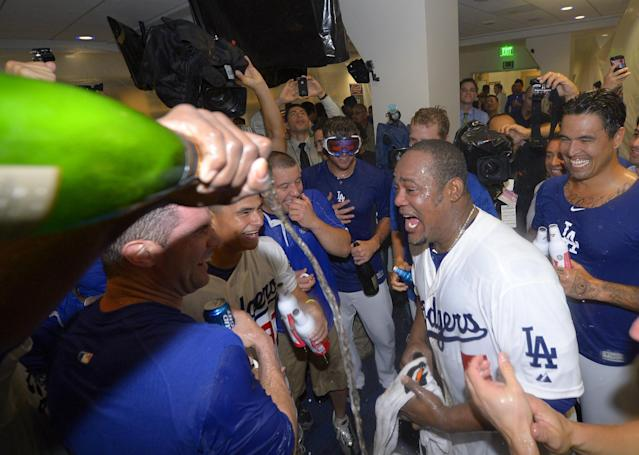 Los Angeles Dodgers' Juan Uribe, second from right, celebrates with teammates in the clubhouse after the Dodgers defeated the Atlanta Braves 4-3 in Game 4 of the National League baseball division series, and advanced to the NL championship series, Monday, Oct. 7, 2013, in Los Angeles. Uribe hit a two-run home run in the eighth inning to put the Dodgers ahead. (AP Photo/Mark J. Terrill)