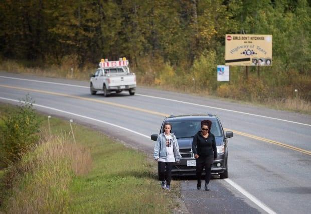 Two women, part of a group of family members and advocates of missing and murdered Indigenous women and girls, walk along a section of the so-called Highway of Tears in Moricetown, B.C., on Sept. 25, 2017.  (Darryl Dyck/The Canadian Press - image credit)