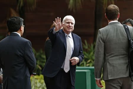 U.S. Senator John McCain waves to members of the media after his meeting with India's Foreign Minister Sushma Swaraj in New Delhi J