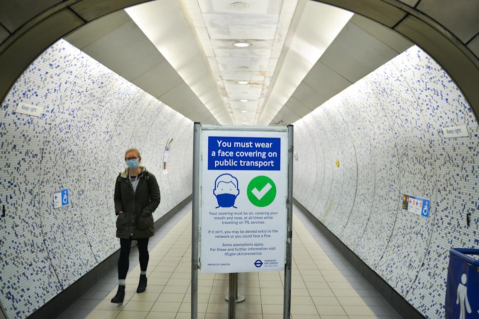 A woman wearing a face mask walks through the London Underground with a sign encouraging the public to use face-coverings at Green Park.