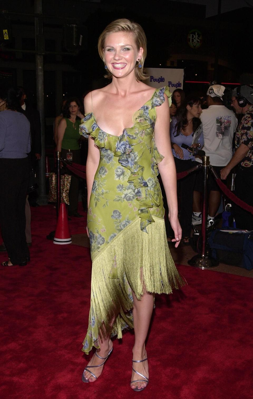 """<p><a class=""""link rapid-noclick-resp"""" href=""""https://www.popsugar.com/Kirsten-Dunst"""" rel=""""nofollow noopener"""" target=""""_blank"""" data-ylk=""""slk:Kirsten Dunst"""">Kirsten Dunst</a>, aka Torrance Shipman, wore a green floral off-the-shoulder dress that would be completely appropriate with a similar strappy metallic heel today. The asymmetric fringe skirt was a sight to see from all angles, and the backless design added extra sex appeal.</p>"""