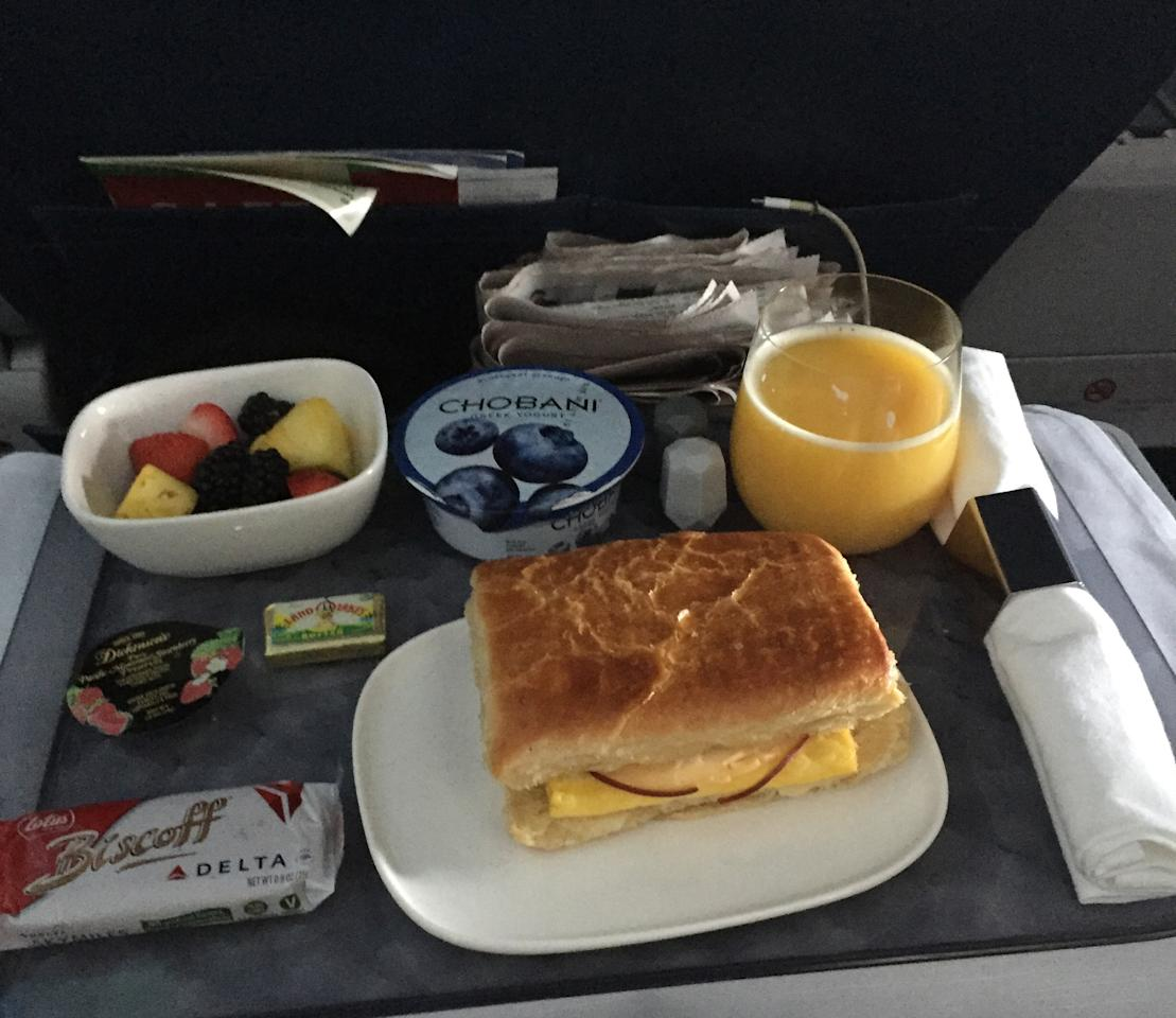 This Thursday, May 11, 2017, photo, shows a breakfast of a bacon, egg and cheese sandwich, yogurt and fruit while seated in first class during a Delta Air Lines flight from New York to Orlando, Fla. Summer travelers may well find themselves stuck in long security lines and squeezed into cramped seats. For frequent travelers, or those who can and want to pay extra, perks are available including upgrades to first-class seats, airport lounges and free food. (AP Photo/Scott Mayerowitz)