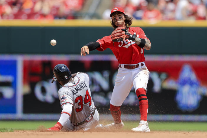 Atlanta Braves' Abraham Almonte, left, is forced out at second base as Cincinnati Reds' Jonathan India, right, fields the ball and throws to first base during the fourth inning of a baseball game in Cincinnati, Sunday, June 27, 2021. (AP Photo/Aaron Doster)