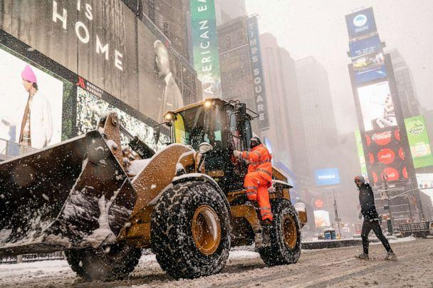 PHOTO: City workers clear streets as pedestrians walk through a snowstorm in Times Square, Feb. 1, 2021, in New York City. (John Minchillo/AP)