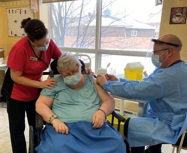 Nicole Laplante, centre, receives a dose of a COVID-19 vaccine in Embrun, Ont., Jan. 13, 2021.