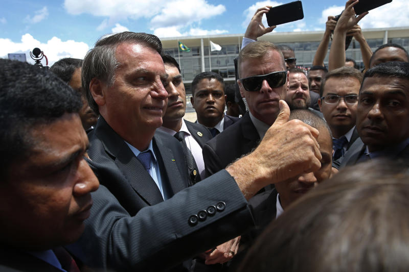Brazil's President Jair Bolsonaro flashes a thumbs up as he greets supporters after attending a Changing of the Guard at the Planalto Presidential Palace, in Brasilia, Brazil, Thursday, Nov. 28, 2019. (AP Photo/Eraldo Peres)