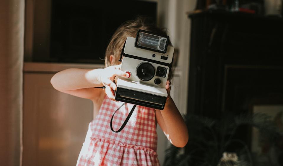 Young girl holding a vintage instant camera and taking a photograph. She presses the red shutter button and looks towards the camera. Face is obscured. Home interior provides a space for copy.