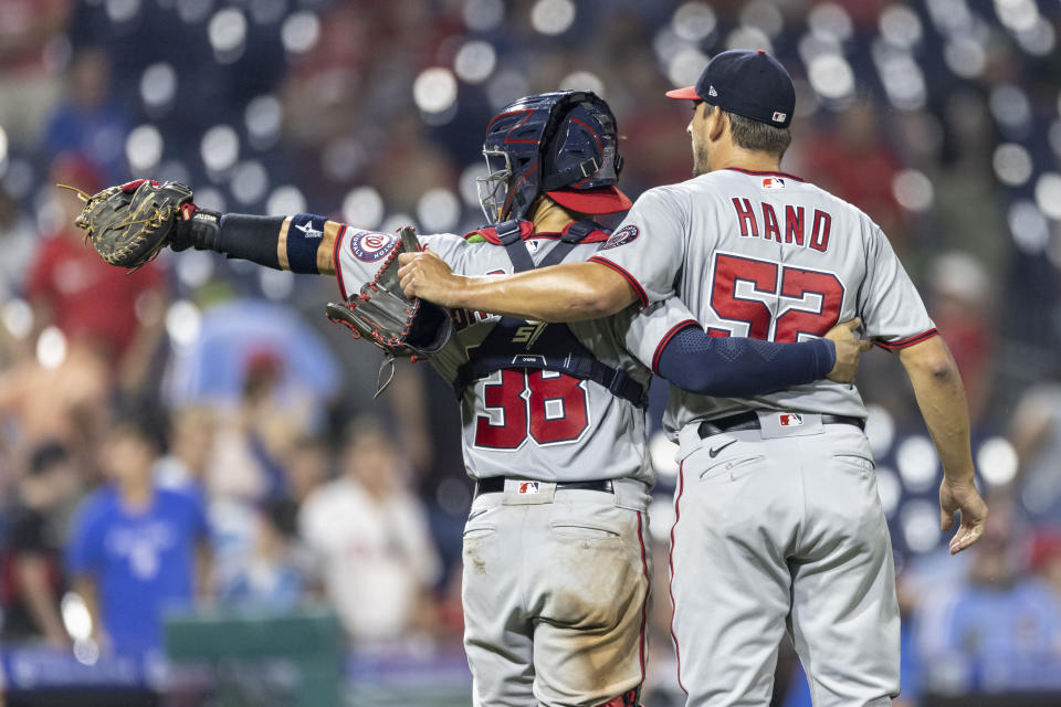 Washington Nationals closing pitcher Brad Hand (52) and catcher Tres Barrera (38) wave to the dugout after the Nationals defeated the Philadelphia Phillies 6-4 in a baseball game Tuesday, July 27, 2021, in Philadelphia. (AP Photo/Laurence Kesterson)