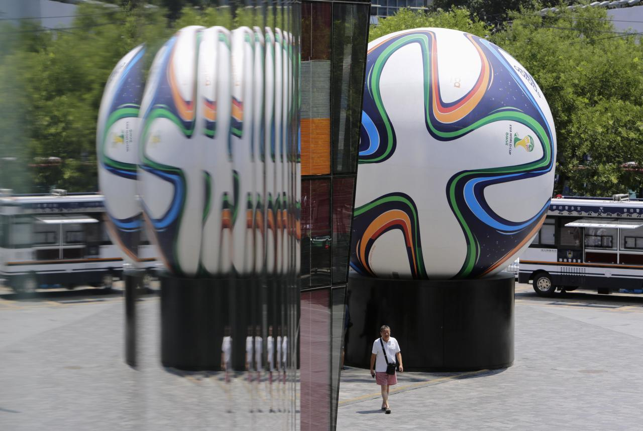 A man walks in front of a sculpture of the Brazuca soccer ball, the official match ball of the World Cup 2014, outside a sports shop at Beijing's Sanlitun area, June 23, 2014. REUTERS/Jason Lee (CHINA - Tags: SPORT SOCCER WORLD CUP BUSINESS)