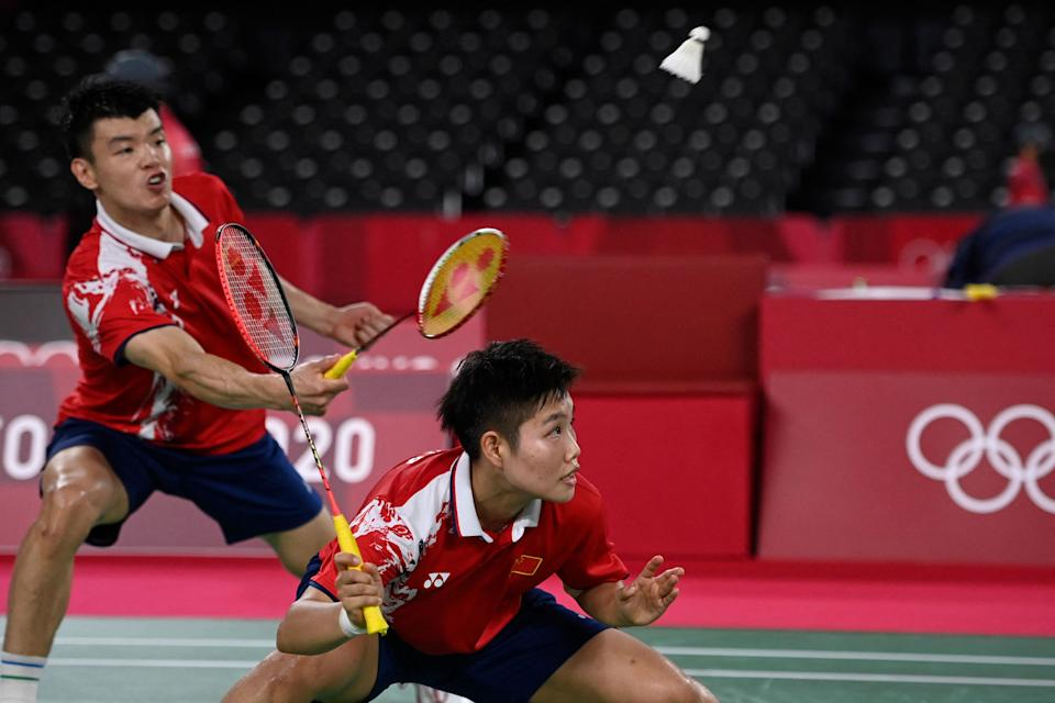 <p>China's Wang Yilyu (L) hits a shot next to China's Huang Dongping in their mixed doubles badminton semi-final match against Japan's Arisa Higashino and Japan's Yuta Watanabe during the Tokyo 2020 Olympic Games at the Musashino Forest Sports Plaza in Tokyo on July 29, 2021. (Photo by Alexander NEMENOV / AFP)</p>