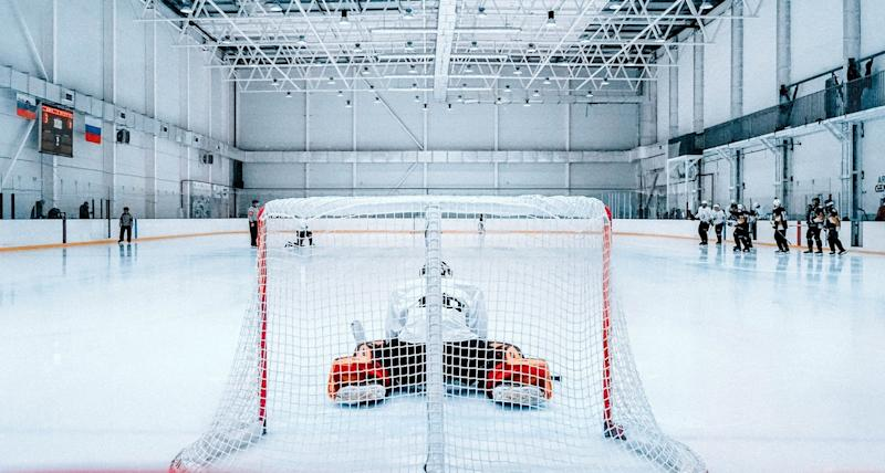 A goalie stretches in the foreground as hockey players in the background get ready to practice.