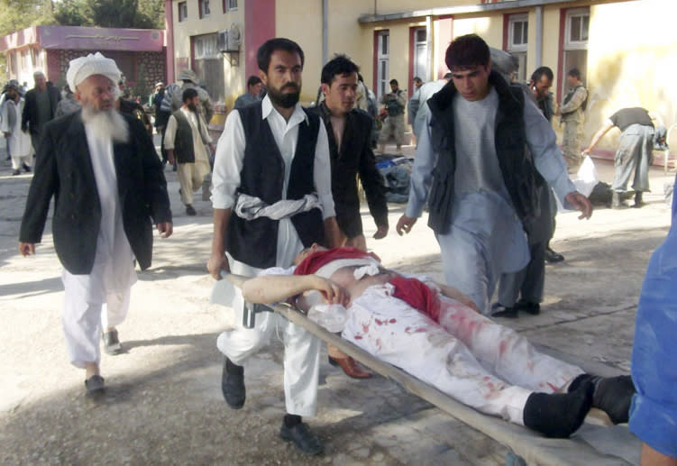 Afghans carry the body of a suicide attack victim at the hospital in Maymana, Faryab province, north west of Kabul, Afghanistan, Friday, Oct. 26, 2012. A suicide bomber blew himself up outside a mosque in northern Afghanistan on Friday, killing dozens of people and wounding scores, government and hospital officials said. (AP Photo/Qawtbuddin Khan)