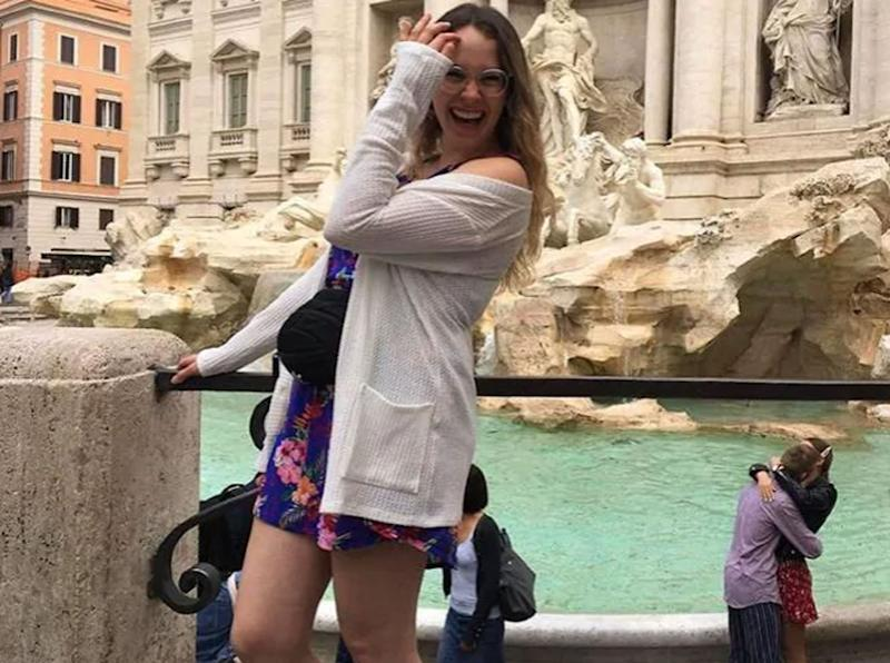 Alycia Savard-Ouellet in front of Trevi Fountain in Italy while a couple kiss behind her.