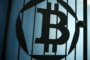 A Bitcoin (virtual currency) logo is pictured on a door at La Maison du Bitcoin in Paris