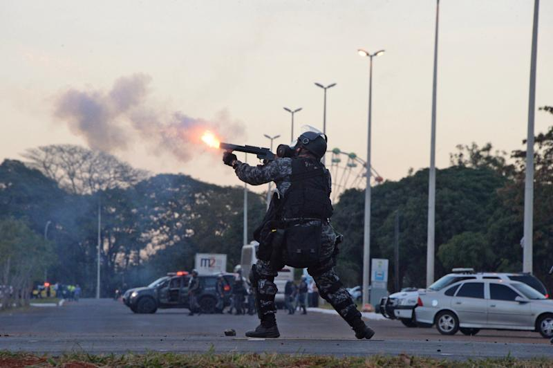 A riot policeman confronts protesters during clashes