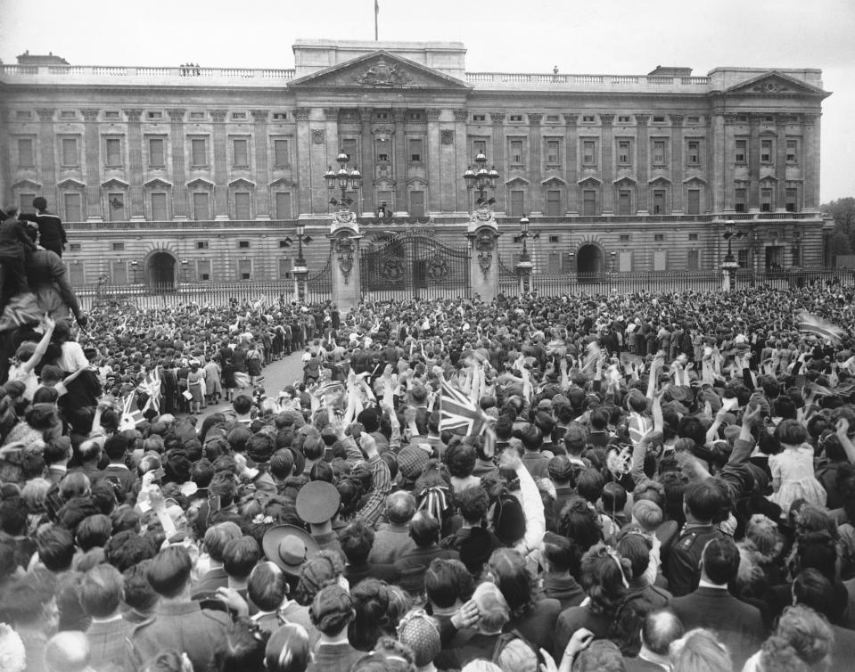 (Original Caption) V.E. Day In London. The crowd gathered outside Buckingham Palace, cheer and wave as their Majesties the King and Queen with the Princesses Elizabeth and Margaret Rose, appear on the balcony. 8th May 1945. (Photo by © Hulton-Deutsch Collection/CORBIS/Corbis via Getty Images)