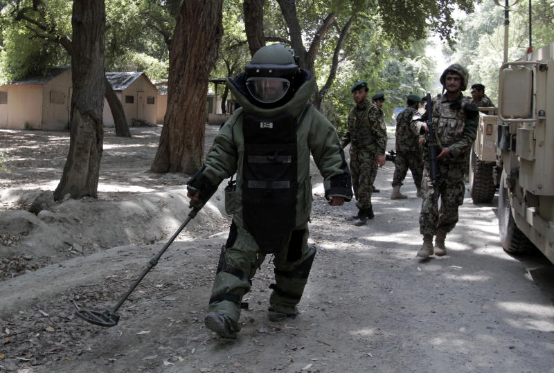 In this Tuesday, Aug. 27, 2013 photo, Afghan army soldier Ali Raza, 30, searches for land mines with a metal detector during an IED, or improvised explosive device, defusing training exercise in Jalalabad, east of Kabul, Afghanistan. After 12 years of war, roadside bombs are the No. 1 killer, claiming thousands of lives every year. As foreign troops wind down operations in preparation for their withdrawal at the end of 2014 insurgents are using an ever larger number of these explosives to assert their grip and recapture territory. (AP Photo/Rahmat Gul)