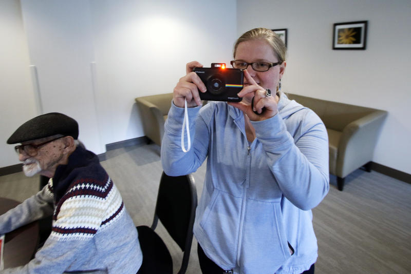 Masha Gregory, an accomplished photographer and artist who is autistic takes a polaroid photo in the recreation room at her apartment complex in Heidelberg, Pa., Thursday, March 30, 2017. Innovative housing developments like this are popping up across the U.S. to serve those who were diagnosed with autism spectrum disorder as children amid increased awareness about the disorder and changes in how it's defined. ( Photo/Gene J. Puskar)