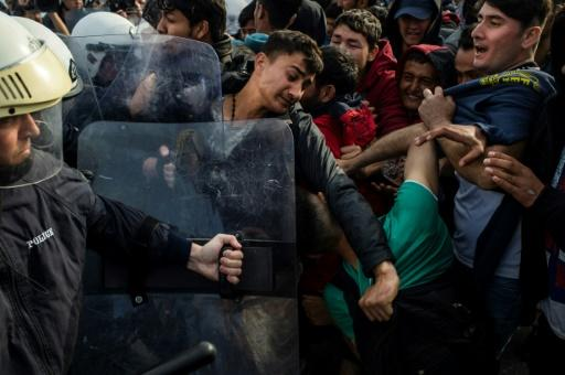 Migrants and refugees scuffle with riot police on the Greek Aegean island of Lesbos