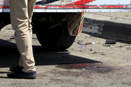 Bloodstains are seen on the ground as security officials inspect the scene of a car bomb blast on a bridge in the Cairo district of Zamalek, April 5, 2015.  REUTERS/Mohamed Abd El Ghany