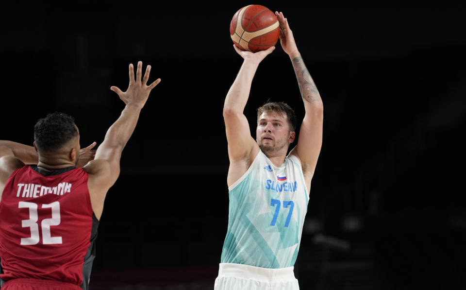 Slovenia's Luka Doncic (77), right, shoots over Germany's Johannes Thiemann (32) during men's basketball quarterfinal game at the 2020 Summer Olympics, Tuesday, Aug. 3, 2021, in Saitama, Japan. (AP Photo/Eric Gay)