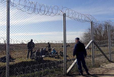 Migrants rest as a policeman watches them near Hungary's border fence on the Serbian side of the border near Morahalom, Hungary, February 22, 2016. REUTERS/Laszlo Balogh