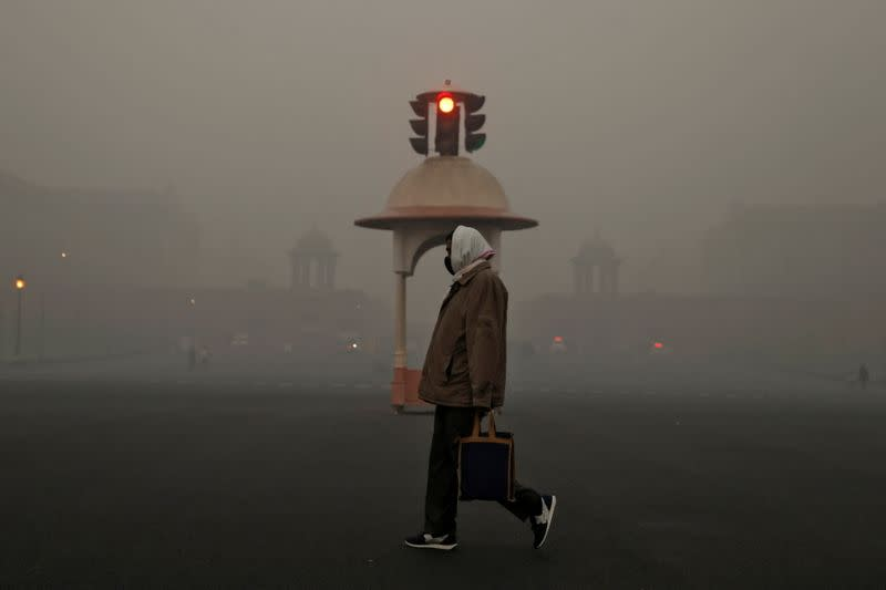 An office-goer walks past a traffic signal near various federal government ministries on a smoggy morning in New Delhi