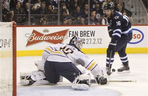 Buffalo Sabres goaltender Ryan Miller deflects a shot by Winnipeg Jets' Andrew Ladd (16) during the second period of an NHL hockey game in Winnipeg, Manitoba, Monday, March 5, 2012. (AP Photo/The Canadian Press, Trevor Hagan)