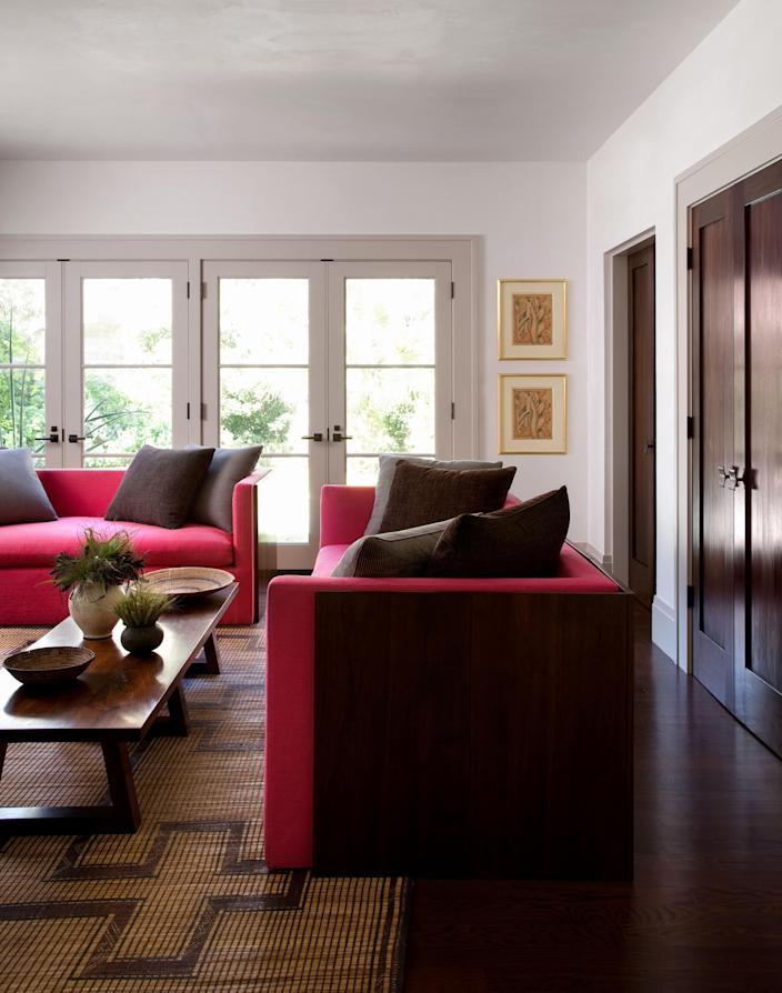 """<div class=""""caption""""> Custom sofas upholstered in hand-dyed pink linen are wrapped in movable walnut screens—a nod to Jean-Michel Frank—made by Erik Gustafson for Juniper Tedhams. The 1940s Tuareg carpet of woven straw and leather is from FJ Hakimian. Artwork by John Storrs. </div>"""