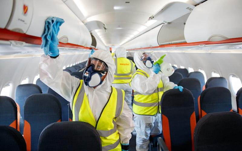A handout photo issued by EasyJet of new bio security measures taking place on an EasyJet plane - EasyJet/Ben Queenborough