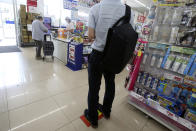 A customer keeps social distancing as he waits at the checkout at a supermarket in Yokohama, near Tokyo, Thursday, May 28, 2020. Japanese Prime Minister Shinzo Abe lifted a coronavirus state of emergency on Monday, ending the restrictions nationwide as businesses begin to reopen. (AP Photo/Koji Sasahara)