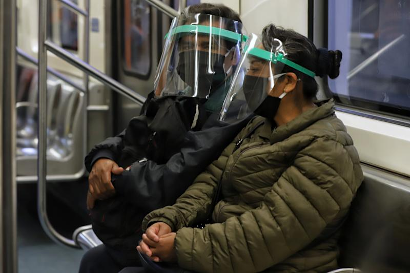 MEXICO CITY, MEXICO - JUNE 29: Metro passengers wear a protective face plastic shield donated by the government on June 29, 2020 in Mexico City, Mexico. As ICU occupancy trends downward, authorities downgraded the alert level from red to orange in Mexico City. Economic activity starts reopening gradually following a staggered schedule, with restrictions and preventive measures. (Photo by Agencia Press South/Getty Images)