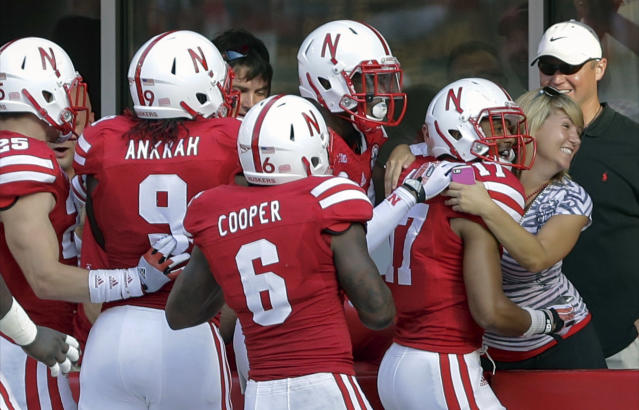 Nebraska fan Jessica Klein, second from right, of Lincoln, right, celebrates with Nebraska cornerback Ciante Evans (17) after he scored a touchdown against Southern Mississippi on an interception in the first half of an NCAA college football game in Lincoln, Neb., Saturday, Sept. 7, 2013. (AP Photo/Nati Harnik)