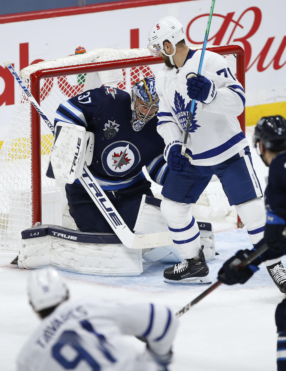 Winnipeg Jets goaltender Connor Hellebuyck (37) makes a save on Toronto Maple Leafs' John Tavares (91) as Nick Foligno (71) applies pressure during the second period of an NHL hockey game Friday, May 14, 2021, in Winnipeg, Manitoba. (John Woods/The Canadian Press via AP)