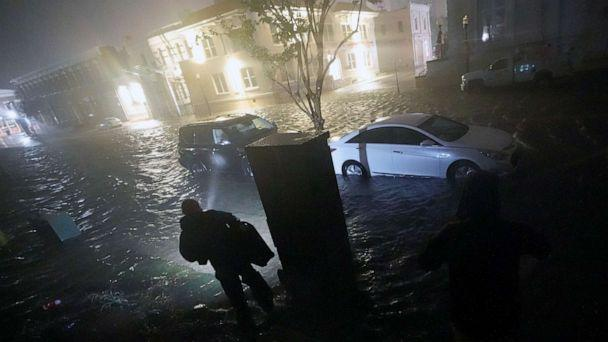 PHOTO:People use flashlights as they walk on flooded streets in search of their vehicle, Sept. 16, 2020, in Pensacola, Fla. (Gerald Herbert/AP)