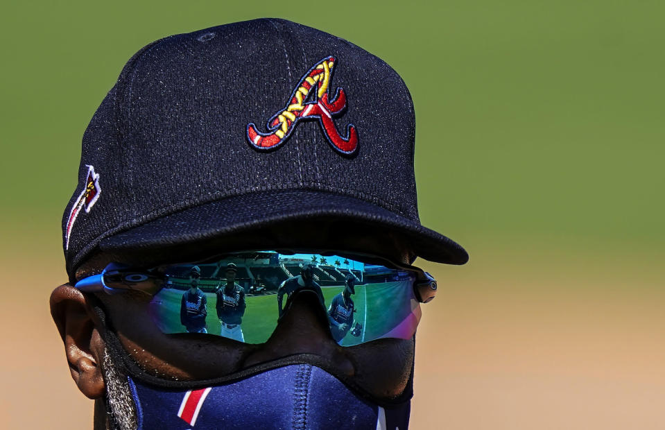 Atlanta Braves first base coach Eric Young talks, from left, Ender Inciarte, Ronald Acuna Jr., Marcell Ozuna and Ozzie Albies, Marcell Ozuna, who are reflected in his sunglasses at spring training baseball practice on Tuesday, Feb. 23, 2021, in North Port, Fla. (AP Photo/Brynn Anderson)