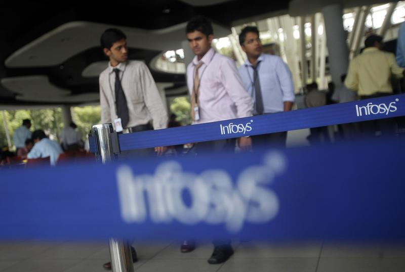 Employees of Indian software company Infosys walk past Infosys logos at their campus in the Electronic City area in Bangalore