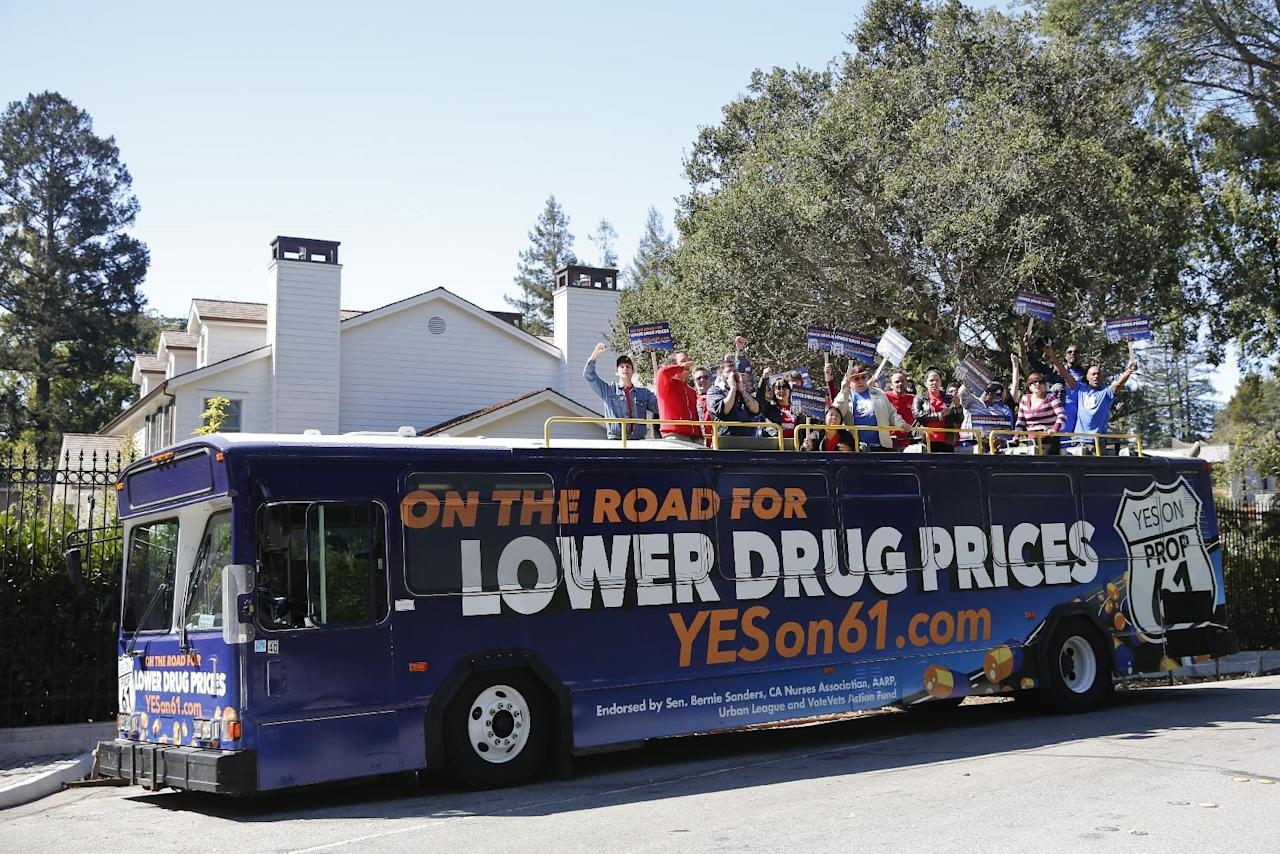 IMAGE DISTRIBUTED FOR AIDS HEALTHCARE FOUNDATION - Advocates for lower drug prices board the Yes on Prop 61 double decker tour bus outside the home of former Gilead CEO John Martin in Hillsborough, Calif., on Thursday, Sept. 29, 2016. (Alison Yin/AP Images for AIDS Healthcare Foundation)