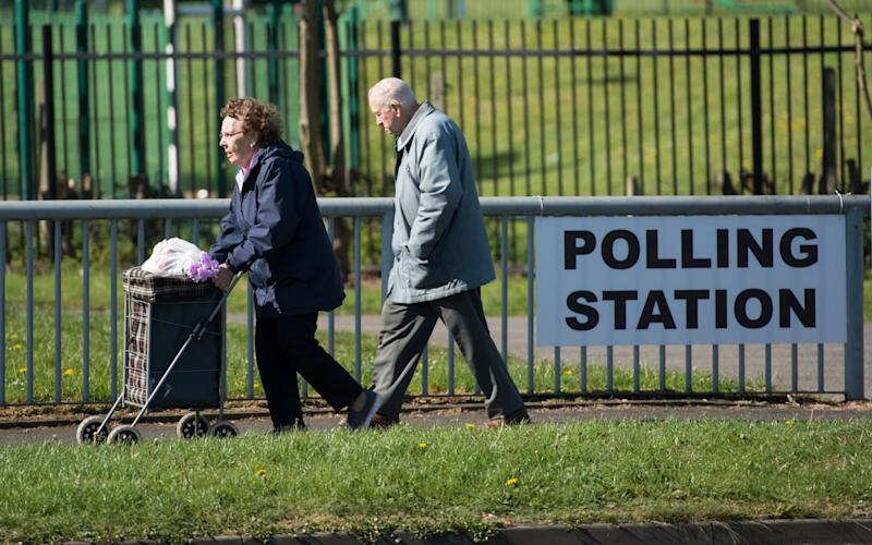 An elderly couple walk past a sign for a polling station - Credit: Oli Scarff/AFP