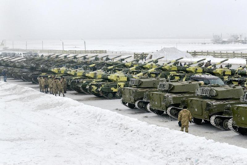 Ukrainian servicemen stand near tanks after a ceremony for the delivery of more than 100 pieces of military equipment, including armoured vehicles, to the Ukrainian armed forces on December 6, 2014 (AFP Photo/Sergey Bobok)