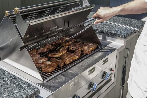 A man holds tongs over steaks on an outdoor propane grill