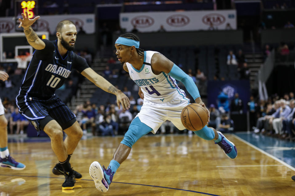 Charlotte Hornets guard Devonte' Graham, right, drives around Orlando Magic guard Evan Fournier during the first half of an NBA basketball game in Charlotte, N.C., Monday, Feb. 3, 2020. (AP Photo/Nell Redmond)